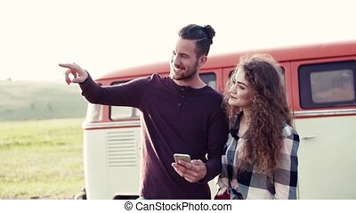 Young couple on a roadtrip through countryside, using map on...