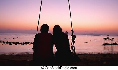 Young couple on a swing at the tropical beach against the sea vacation at sea, look beautiful sunset. slow motion. 1920x1080