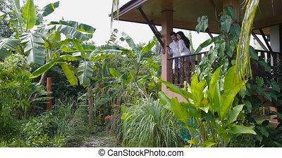 Young Couple On Balcony In Tropical Forest Stnd Embracing...