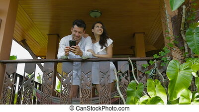 Young Couple On Balcony Looking Up Talking Man And Woman...