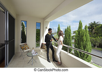 Young couple on balcony - Young couple toasting with ...