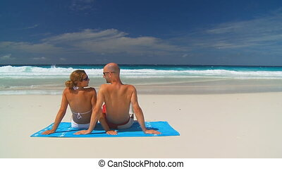 young couple on beach towel