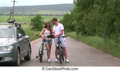 Young couple on bicycles near his car with roof-mounted bike...