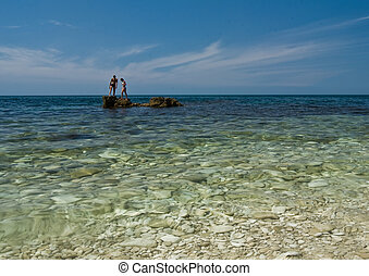 Young couple on big stones in clear sea