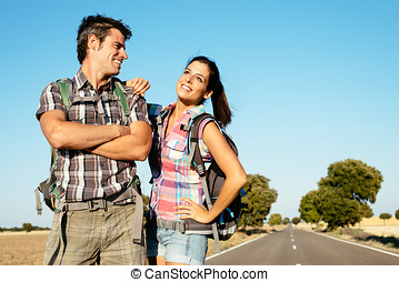 Young couple on hiking travel - Young couple hiking on road...