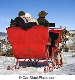 Young couple on sleigh ride.