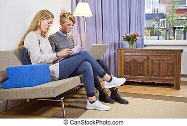 Young couple on sofa doing their personal administration
