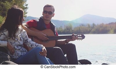 Young couple on the beach playing guitar singing song on a summer day next to mountain river. 3840x2160