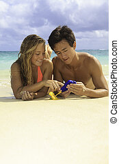 couple on the beach with their cell phone