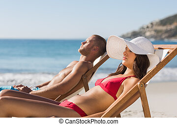Young couple on their deck chairs having a nap on the beach