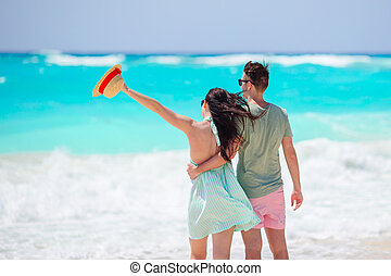 Young couple on white beach. Family vacation