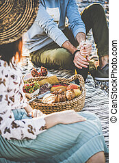 Young couple opening bottle of sparkling wine at summer picnic