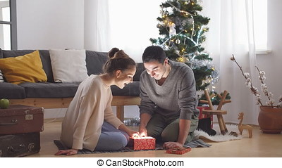 Young couple opens a Christmas gift.