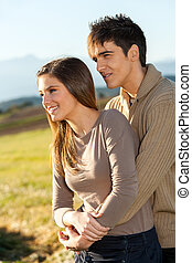 Young couple outdoors in rural field.