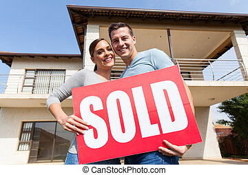 young couple outdoors with sold sign