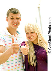 Young couple outdoors with thumbs up