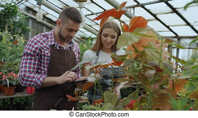 Young couple owners work in garden center. Attractive man...