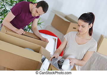 young couple packing boxes