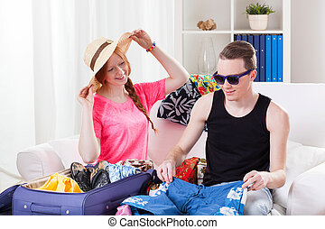 Young couple packing luggage