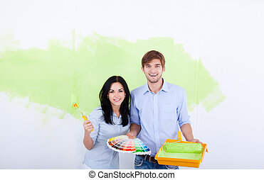 young couple paint at home wall - young couple paint wall...