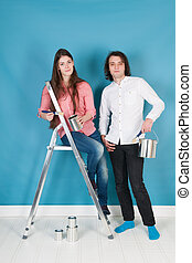 Young couple painting house