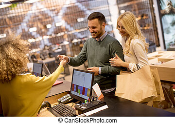 Young couple paying female sales assistant with credit card in clothes shop