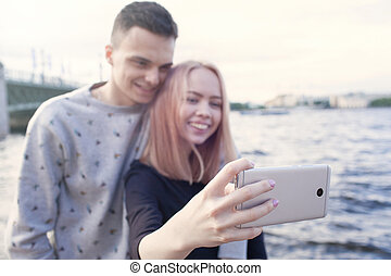 Young couple photographing a selfie with smartphone on the background of the urban landscape. River embankment in Saint Petersburg