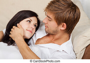 young couple - beautiful young couple sitting on a sofa