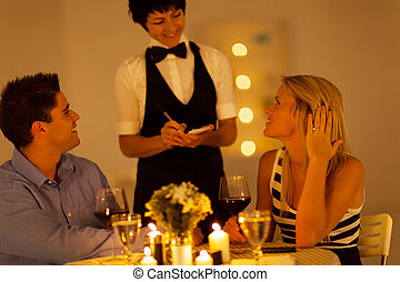 young couple place dinner order to waitress in a restaurant