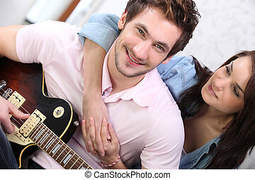 Young couple playing a guitar at home