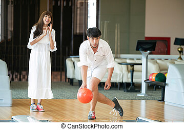 Young couple playing bowling at the sport club.