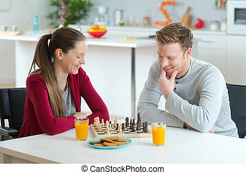 young couple playing chess in a home interior