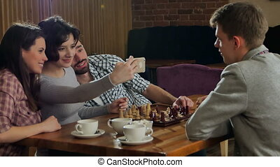 Young couple playing chess indoor with friends and taking selfie