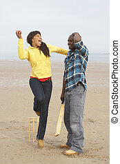 Young Couple Playing Cricket On Autumn Beach Holiday