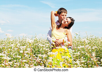 Young couple playing on field of flowers in sunny day -...
