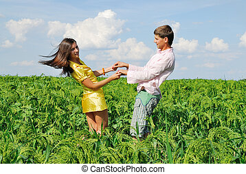Young couple playing on green field