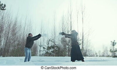 Young couple playing outdoors in the snow.