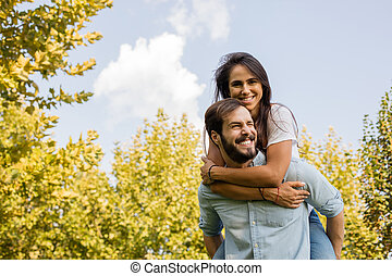 young couple playing outside in park