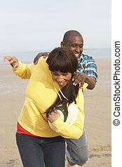 Young Couple Playing Rugby On Autumn Beach Holiday