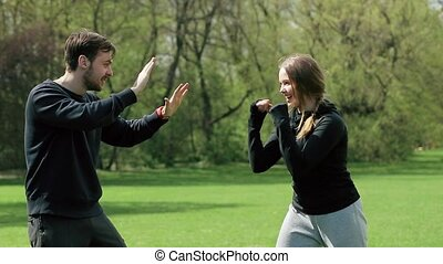 Young Couple Playing Together Boxing Outdoors