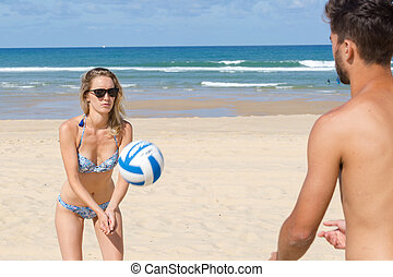 young couple playing volley ball on the beach
