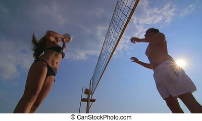 Young couple playing volleyball on summer beach in the sun
