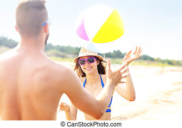 Young couple playing with a ball at the beach