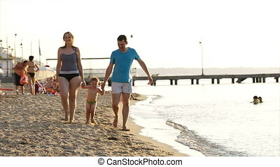 Young couple playing with their son at the seaside