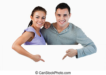 Young couple pointing at advertisement below them against a...
