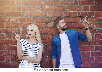 Young couple pointing on the brick wall