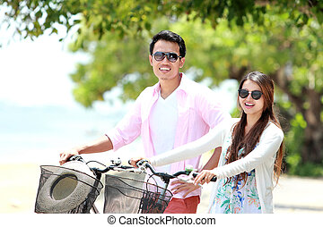 Young couple portrait with bicycle on the beach