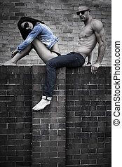 Young Couple Posing on Concrete Wall