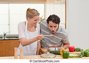 Young couple preparing a sauce