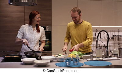 Young couple preparing food in kitchen.
